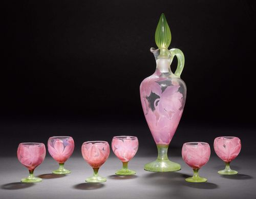 EMILE GALLE DECANTER WITH 6 SMALL GLASSES, ca. 1900. Colourless glass with pink and violet overlay, etched, applied and fire-polished. Baluster-shaped decanter with applied handle. Stopper and foot, striped yellow green. The 6 small glasses with round foot. Decorated with clematises. All items signed Gallé. One glass restored. H decanter: 34 cm. H glasses: 7 cm.