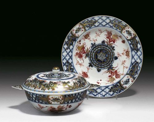 DOUBLE-HANDLED BOWL WITH COVER AND STAND, Meissen, circa 1730. Painted in Imari style in underglaze-blue and iron-red picked out in gilding, with Indian flowers and lattice work, crossed swords in underglaze-blue to inside of bowl and back of the stand. Bowl 16cm, stand 22cm. Provenance: Private collection, Basel.