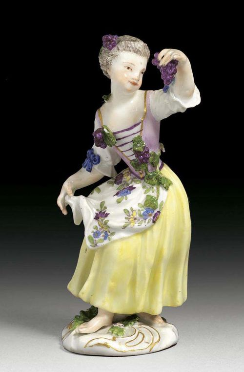 GIRL WITH GRAPES, Meissen, um 1750. With a violet waist coat applied with grapes, over yellow skirt with flowered apron and wine in her left lifted hand, crossed swords in underglaze-blue, 13cm, slightly chipped.