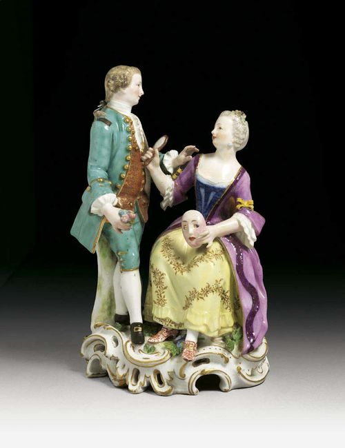 GROUP OF A LADY AND A GENTLEMAN, Meissen, circa 1763-74. She seated with a mask in her left hand, a mirror in her right, the gentleman standing to her right, his hand reaching out to her, crossed swords and dot in underglaze-blue, impressed B.S.z.94z., 20cm, small restorations.