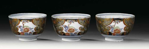 THREE CUPS WITH 'IMARI' DECORATION, Meissen, circa 1740. Painted in Imari style, with Asian style floral reserves, crossed swords and painter's mark K in underglaze-blue, impressed number 52.