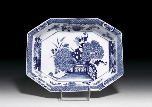 BASIN, Meissen, circa 1740. Octagonal form, painted in underglaze-blue in Chinese style with chrysanthemum and peony flowers in a fenced garden, crossed swords and K in underglaze-blue, impressed numeral 26, 32,5x25cm. Slightly chipped.