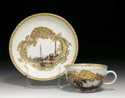 CUP AND SAUCER, Meissen, circa 1745. Painted with a Kauffahrteiscene and landscape setting with figures in gilt lattice work cartouches picked out in black, the interior of the cup with a landscape scene in purple camaïeu, crossed swords in underglaze-blue, gilt numeral 39 to both pieces, small chip to saucer, gilding slightly rubbed.