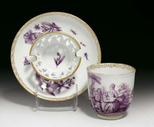 TREMBLEUSE CUP AND SAUCER, Meissen, circa 1745. Painted in purple camaïeu, the cup with a Watteau scene, the saucer with a pierced stand painted with ombrierte flowers and insects, rims with gilt lace borders, crossed swords in underglaze-blue, impressed numeral 6 to cup, painters mark G in gilding, associated.