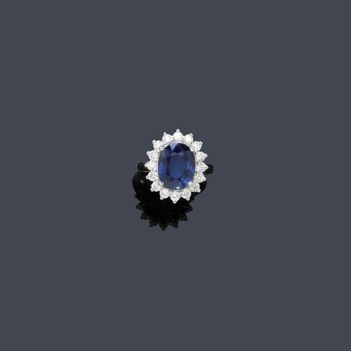 SAPPHIRE AND DIAMOND RING. White gold 750. Decorative ring, the top set with 1 oval sapphire of ca. 5.50 ct, within a border of 16 brilliant-cut diamonds weighing ca. 1.00 ct. Size ca. 53. Matches the previous lot.