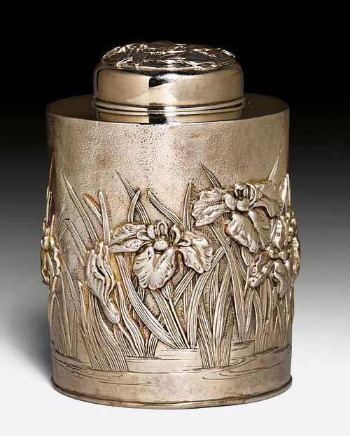 A SILVER TEA CADDY WITH REPOUSSE IRIS DECORATION.