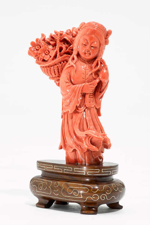 A CARVED CORAL FIGURE OF A GIRL WITH A FLOWER BASKET.