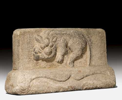 A GREY STONE RELIEF CARVED WITH A MYTHICAL BEAST.