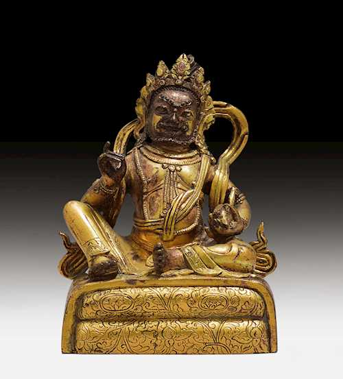 A GILT BRONZE FIGURE OF KUBERA.