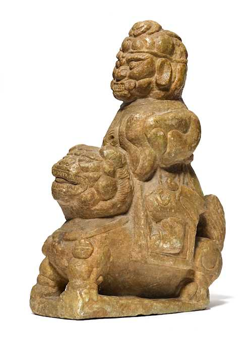 A FIERCE GUARDIAN FIGURE ASTRIDE A LION.