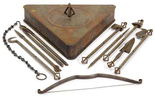 A SET OF RITUAL INSTRUMENTS IN A TRIANGLE-SHAPED BOX.
