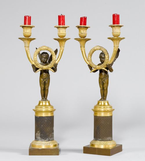 "PAIR OF CANDELABRAS GIRANDOLEN ""A L'ANGELOT"",Empire, Paris, ca. 1810/15. Matte and polished gilt bronze, and burnished bronze. Cupid standing on a half-sphere, bearing a laurel wreath with 2 curved light branches with broad drip pans and vase-shaped nozzles. H 41.5 cm."