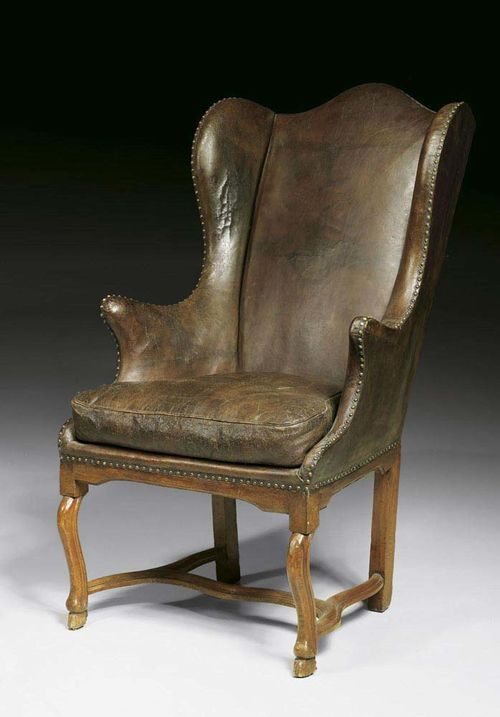 WING BACK CHAIR, Louis XV, German, 18th century Moulded walnut, fully upholstered with brown leather covers and decorative nailwork, with cushion. 71x50x55x124 cm. Provenance: Private collection, Munich