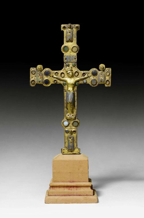 PROCESSIONAL CROSS,Limoges, early 13th century. Wooden core mounted with chased and gilt copper, set with glass stones and champleve enamel plaques in turquoise, dark blue, red and green. The Corpus Christi in engraved, gilt and enameled copper. One side of the cross with the crucified Christ and half-figures of the Evangelists at the cross ends. Verso with round, enamel plaque of Christ in Majesty. The cross ends with the symbols of the Evangelists. Losses and chips. Supplements. H 41 cm.