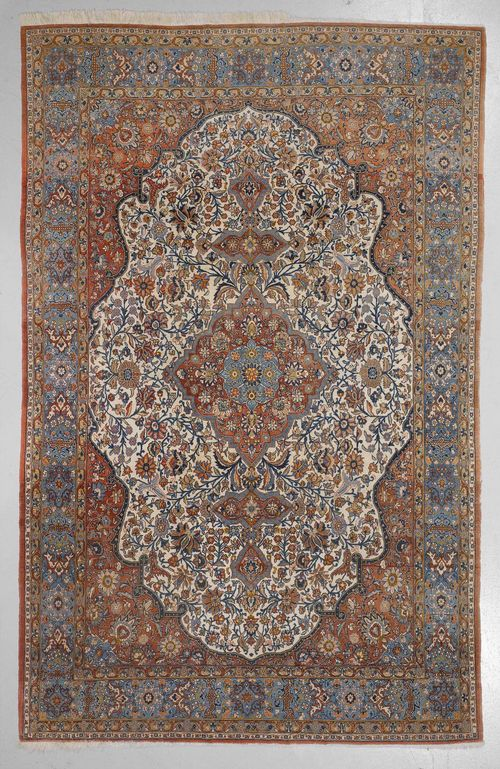 GHOM old.Bulky, white and rust coloured central medallion on a rust coloured ground, opulently patterned with trailing flowers and palmettes, blue edging, 227x345 cm.