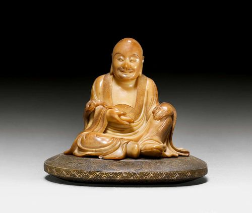 A SOAPSTONE CARVING OF A SEATED LUOHAN ON A OVAL BASE. China, 17th c. Height 9.6 cm. Signature: Wei Rufen zhi. Very minor chips.