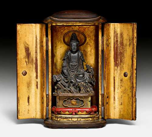 A LACQUERED ZUSHI OF KANNON BOSATSU SEATED ON A ROCK.