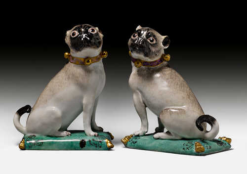 A PAIR OF PUGS ON CUSHIONS,