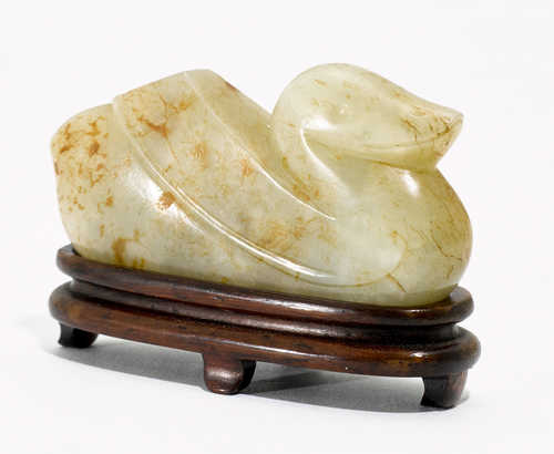A CARVED LIGHT GREEN JADE FIGURE OF A SEATED DUCK.