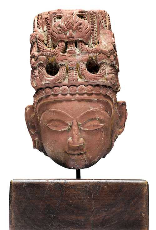 A RED SANDSTONE HEAD OF A DEITY, PROBABLY SURYA.