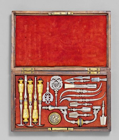 AN ELEGANT TREPANNING SET, France, possibly 19th c. Shaped and engraved, partly gilt steel. Consisting of a trepan with screw-handle showing Chronos, 7 drill bits, 3 elevators, 5 scrapers, etc. some instruments inscribed IOANNES GANTE. In walnut case with brass mounts lined with red suede (lid warped and cracked). 34.5x20.5x5.2 cm.