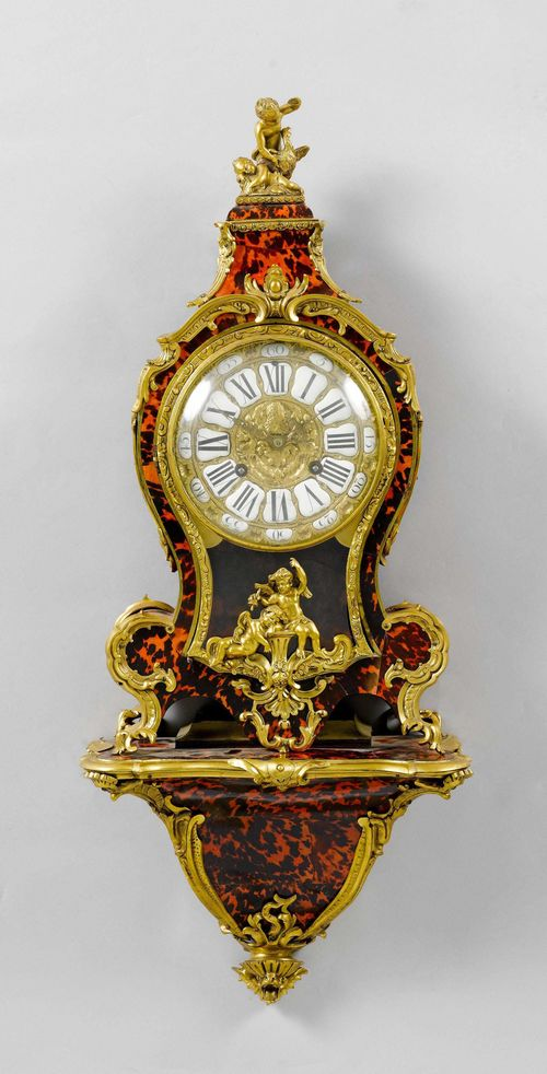 CLOCK ON PLINTH,late Louis XV, France, 19th century. Curved wooden case, decorated with red tortoiseshell. Bronze mounts designed as rocailles, leaves, shells and putti. Bronze dial with white enamel cartouches. Movement with anchor escapement striking the 1/2-hour on bell. H 86 cm. Provenance: - from a Swiss private collection.