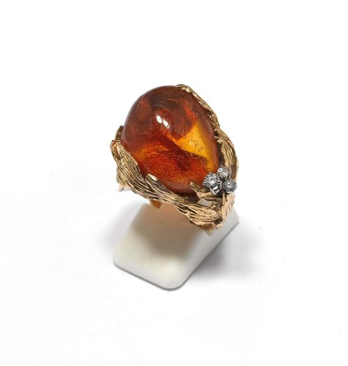 AMBER AND DIAMOND RING, GILBERT ALBERT. Yellow gold 750. Decorative ring, the top set with 1 asymmetrical amber of ca. 22 x 16.5 mm and additionally decorated with 3 diamonds weighing ca. 0.10 ct. Size ca. 56. With copy of insurance estimate, 1985.