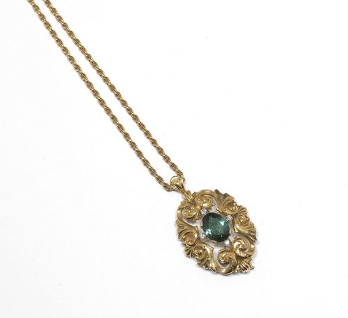 TOURMALINE AND DIAMOND PENDANT / BROOCH, WITH CHAIN, ca. 1960. Yellow gold 750, 50g. Decorative, oval pendant with a leaf volute decor, set with 1 fine tourmaline weighing ca. 7.00 ct within a border of 4 brilliant-cut diamonds weighing ca. 0.32 ct. On a fine fantasy chain, L ca. 45 cm.