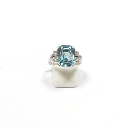 ZIRCONIA AND DIAMOND RING. Platinum. Classic-elegant ring, the top set with 1 step-cut, blue-green zirconia weighing ca. 9.50 ct, signs of wear, the shoulders additionally decorated with a total of 6 diamonds weighing ca. 0.20 ct. Size ca. 57. With copy of insurance estimate, 1985.