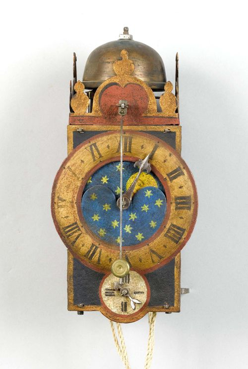 IRON CLOCK WITH MOON PHASE AND FRONT PENDULUM,Germany, 17th century. Closed, rectangular metal case with bell on top. Dial ring for the hours with piercing for the moon phase disk. Smaller dial ring for the minutes below. Clockwork mechanism and striking mechanism arranged one behind the other, striking the 1-hour on bell. H 27 cm. Painting, later. Formerly, probably with wheel balance.
