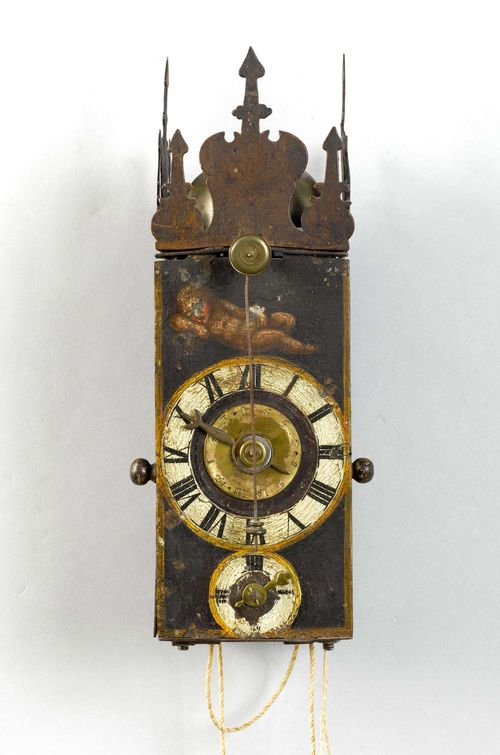 IRON CLOCK WITH FRONT PENDULUM AND ALARM,Baroque, Switzerland or Germany, 17th century. Closed metal case, painted with a reclining putto and 2 depictions of saints on the lateral doors. Pierced top. Painted dial with alarm disk, dial for the minutes below. Clockwork mechanism and striking mechanism arranged one behind the other. Movement with verge escapement striking the 1/2-hour on bell. Alarm on bell. H 26 cm. Painting, rubbed. Movement with alterations.