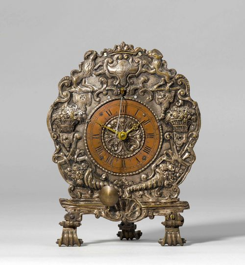 TABLE CLOCK WITH FRONT ZAPPLER,Baroque, Southern Germany, probably Augsburg, beginning of the 18th century. Brass sheet metal chased with baskets with flowers, cornucopias, volutes and a coat-of-arms held by lions, and silver-plated. Copper dial ring. Movement with verge escapement. H 26 cm. Silver-plating, rubbed. Provenance: - from a Zurich private collection.
