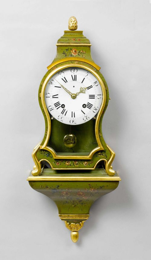 PAINTED CLOCK ON PLINTH,Neuchâtel, end of the 18th century. The movement signed N. GIRARDIN À LUXEUL. Wooden case, painted green and decorated with flowers. Enamel dial . Movement with verge escapement striking the 1/2-hour on bell. H 90 cm. Movement and case combined later.