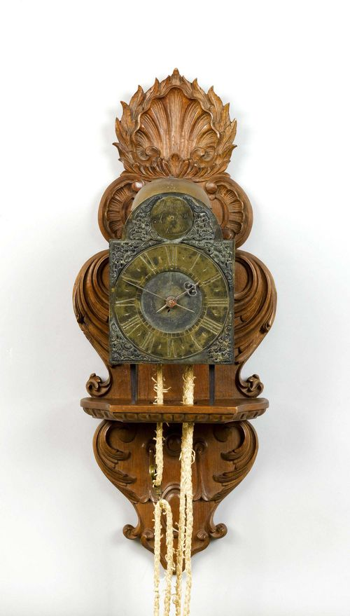 IRON CLOCK,England, 18th century. The dial inscribed WILLIAM JOURDAIN LONDON. Open case. Brass dial ring. Movement with anchor escapement striking the 1/2-hour on bell.  H 34 cm. On a later, carved wooden console. Pendulum, later.