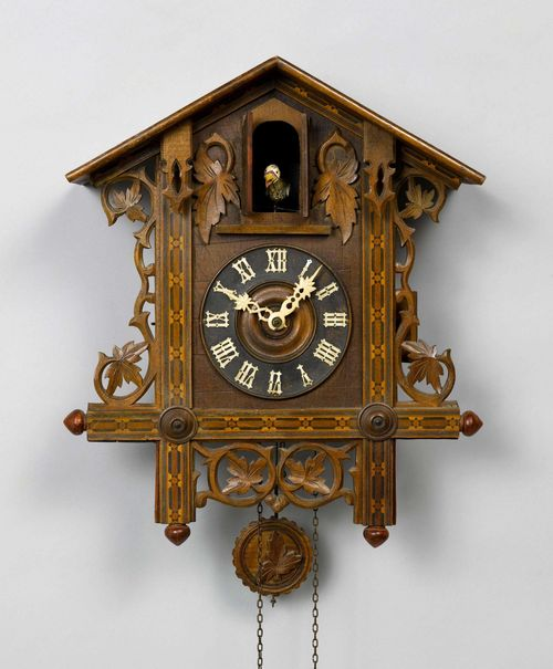 CUCKOO CLOCK,Black Forest, ca. 1900. Pinewood. Case designed as a house with pierced tendrils. Movement with anchor escapement and cuckoo call as well as strike on gong. H 46 cm.