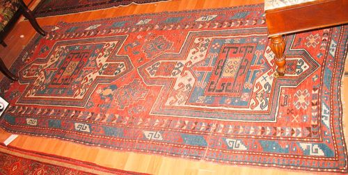 FACHRALO old.Red ground with two medallions, the entire carpet is geometrically patterned with depictions of plants, human beings and animals, triple stepped border, signs of wear, 240x115 cm.