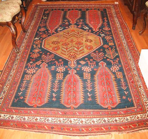 GASCHGAI antique, dated 1927.Dark blue central field with a green central medallion, the ends are decorated with bulky trees of life in red, the entire carpet is patterned with stylized depictions of plants and animals, triple stepped border in red and white, slight wear, 260x150 cm.