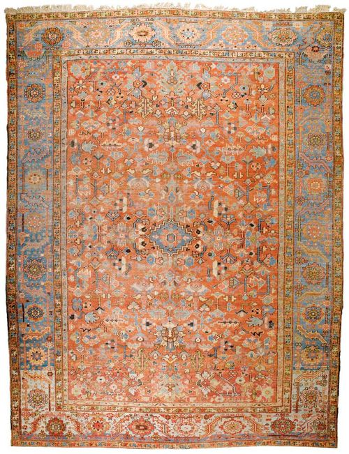 HERIZ antique.Dusky pink central field, patterned throughout with stylized plant motifs in light blue and yellow, blue border, signs of wear, 390x290 cm.