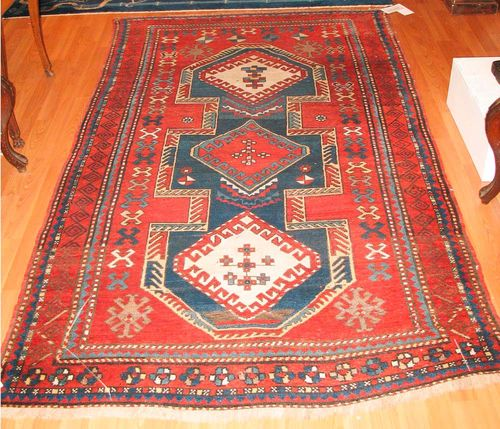 KAZAK old.Red ground with a blue central medallion, geometrically patterned, red border, slight wear, 225x130 cm.
