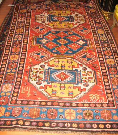 LORI PAMPACH antique.Rust coloured ground with three medallions in white, blue and green, the entire carpet is geometrically patterned with star motifs and animals, blue border, good condition, 220x140 cm.
