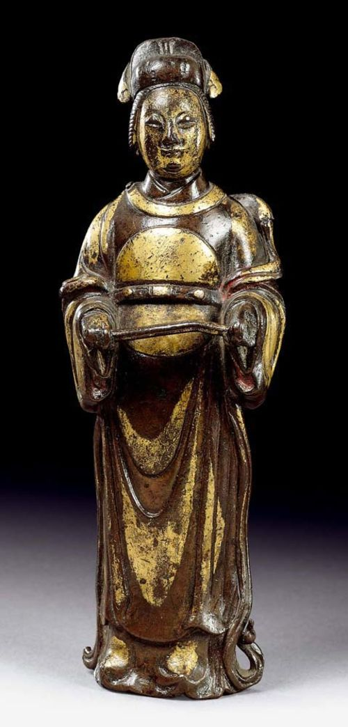 STANDING CIVIL SERVANT.China, Ming Dynasty, 15.5 cm. Finely-cast bronze with partial fire gilding and traces of red lacquer (on the inside of the sleeves). Finely-worked figure with nice contrasts, since the folds of the garment are alternately bronze and gold.