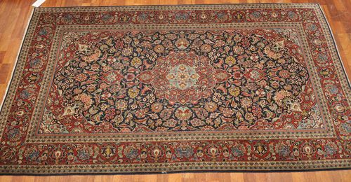 KESHAN old.With a blue central field and red medallion, lavishly patterned with trailing flowers and palmettes and with a red border. Good condition, 135x210 cm.