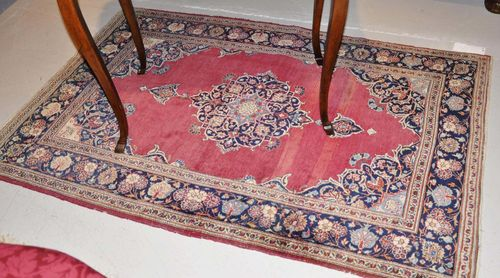 KESHAN old.With a red ground, floral central medallion and dark blue border. Slightly worn, 110x160 cm.