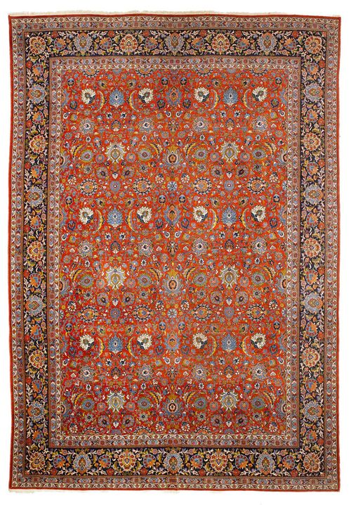 KESHAN antique. The red ground is patterned with trailing flowers and palmettes in harmonious colours. With a black border. Slightly worn, 325x447 cm.