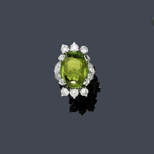 PERIDOT AND DIAMOND RING, ca. 1950. White gold 750. Elegant ring, the top set with 1 very fine oval peridot of ca. 21.00 ct, within a border of 6 brilliant-cut diamonds, 6 navette-cut diamonds and 2 drop-cut diamonds weighing ca. 3.30 ct and set throughout with 56 brilliant-cut diamonds. Total diamond weight ca. 1.00 ct.