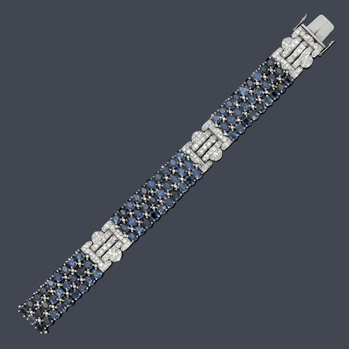 SAPPHIRE AND DIAMOND BRACELET. White gold 750, 72g. Elegant bracelet in the Art Deco style, of 3 geometrically designed ornaments set throughout with 174 brilliant-cut diamonds weighing ca. 2.60 ct and of 4 intermediate links decorated with 84 oval sapphires weighing ca. 20.00 ct and 62 brilliant-cut diamonds weighing ca. 0.50 ct. W ca. 1.6 cm, L ca. 18.5 cm.