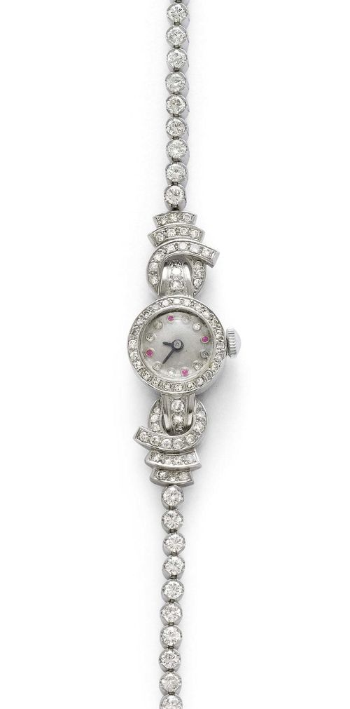DIAMOND LADY'S WRISTWATCH, ca. 1950. White gold 750, 28g. Round case with diamond-set lunette and attaches weighing ca. 1.20 ct. Silver-coloured dial with diamond indices and 4 ruby indices, silver-coloured hands. Hand winder, does not run: resinified. Rivière bracelet set throughout with 30 brilliant-cut diamonds weighing 2.40 ct, L ca. 16.5 cm. D 16 mm.