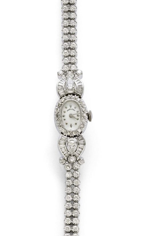 DIAMOND LADY'S WRISTWATCH, HAMILTON, ca. 1950. White gold 585. Oval case No. SD 71602, with diamond lunette weighing ca. 0.30 ct, attaches set with 2 drop-cut diamonds weighing ca. 0.80 ct, 24 baguette-cut diamonds and 6 brilliant-cut diamonds weighing ca. 1.40 ct. Textured dial with silver-coloured indices and hands, signed. hand winder, form movement signed, Cal. USA761. Double-row Rivière bracelet with 62 brilliant-cut diamonds weighing ca. 2.40 ct. L ca. 16.5 cm. D 18 x 14 mm. Matching extension element with two pairs of brilliant-cut diamonds.