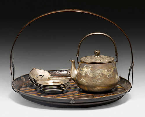 A SILVER TEA SET WITH A COPPER TRAY.