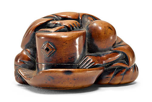 A BOXWOOD NETSUKE OF A SLEEPING FARMER ON A BARREL.